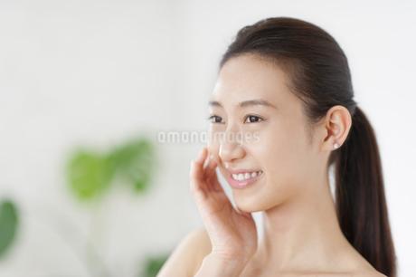 頬に片手を添えて微笑む女性の写真素材 [FYI02966668]
