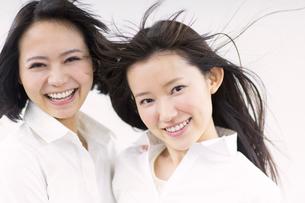 風を受けながら笑う女性2人の写真素材 [FYI02966672]