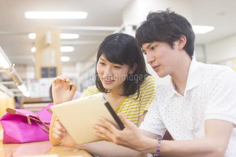 スマートデバイスをみる学生男女の写真素材 [FYI02966685]