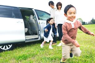 車から降りて草原を走るファミリーの写真素材 [FYI02966686]