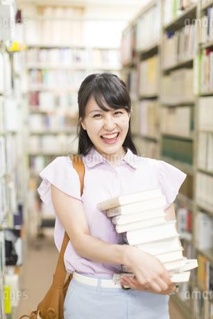図書室で重ねた本を持って微笑む女子学生の写真素材 [FYI02966688]