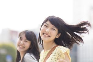 笑顔ではずみながら歩く2人の若い女性の写真素材 [FYI02966689]
