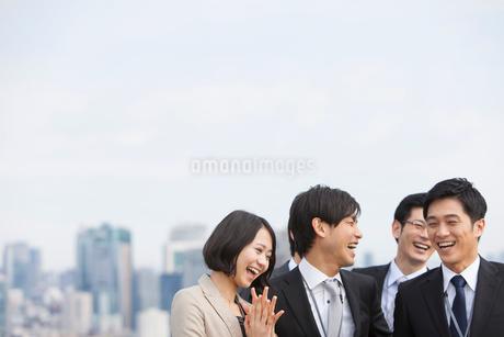 ビル群を背景に笑い合うビジネス男女の写真素材 [FYI02966692]