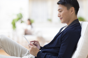 リラックスチェアに座りタブレットPCを見る男性の写真素材 [FYI02966697]