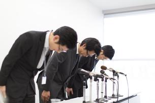 謝罪会見で頭を下げるビジネス男性3人の写真素材 [FYI02966698]