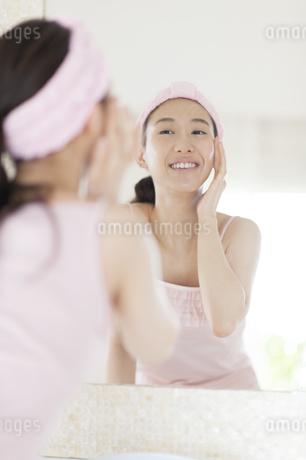 鏡の前でスキンケアをする微笑む女性の写真素材 [FYI02966701]