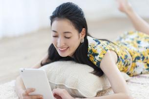 クッションの上でタブレットPCを見る女性の写真素材 [FYI02966705]