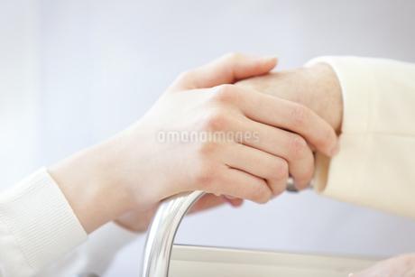 車椅子の患者の手に添える女性看護師の手元の写真素材 [FYI02966707]