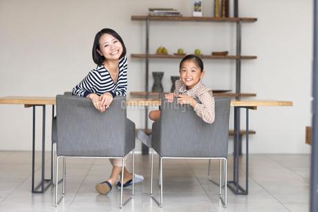 テーブルを背に振り返る母と娘のスナップの写真素材 [FYI02966712]