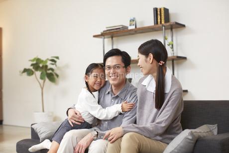 ソファーで笑顔の3人家族の写真素材 [FYI02966713]