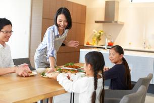 家族に食事を用意する奥さんの写真素材 [FYI02966720]