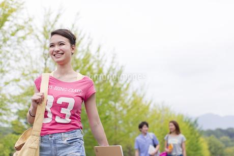 微笑みながらキャンパスを歩く女子学生の写真素材 [FYI02966721]