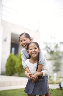 庭で身体を合わせて笑う姉妹のスナップの写真素材 [FYI02966722]
