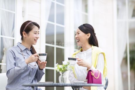 コーヒーカップを手に笑い合う2人の女性の写真素材 [FYI02966728]