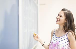 黒板に書いた文字を確かめる女子学生の写真素材 [FYI02966731]