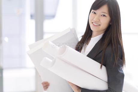 封筒と筒を持って微笑むビジネス女性の写真素材 [FYI02966736]