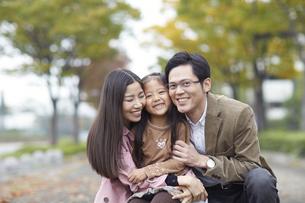 遊歩道でかがみながら微笑む家族のスナップの写真素材 [FYI02966740]