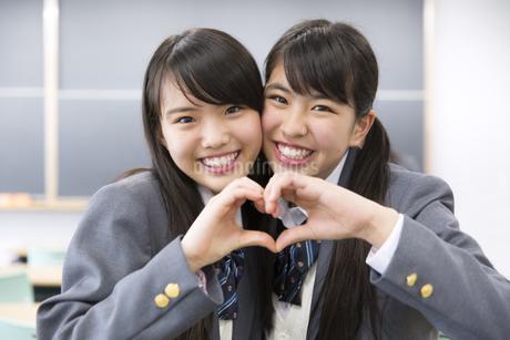 教室で顔を寄せて手でハートを作る2人の女子高校生の写真素材 [FYI02966741]