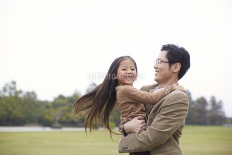 公園で父に抱かれて微笑む女の子の写真素材 [FYI02966744]