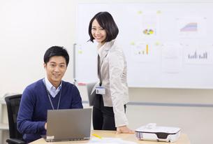 ノートパソコンを前に微笑むビジネス男女の写真素材 [FYI02966746]