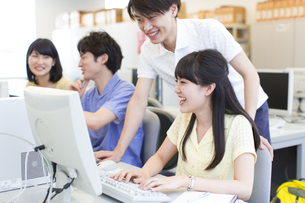 パソコン教室で会話をする学生たちの写真素材 [FYI02966747]