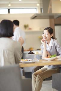 テーブルで食事を前に笑顔で会話する女性の写真素材 [FYI02966748]