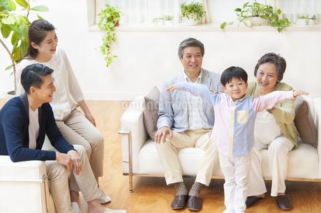 腕を上げる子供と笑い合う家族の写真素材 [FYI02966749]