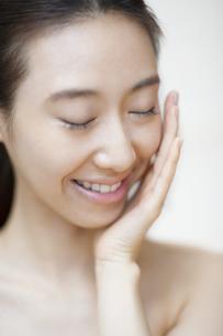 頬に片手を添えて目を瞑り微笑む女性の写真素材 [FYI02966752]