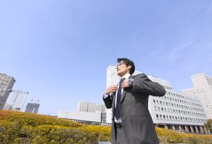 ビルの前で襟に手をやり微笑むビジネス男性の写真素材 [FYI02966753]