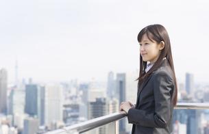 屋上で遠くを見ながら微笑むビジネス女性の写真素材 [FYI02966762]