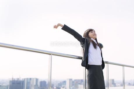 屋上で伸びをするビジネス女性の写真素材 [FYI02966763]