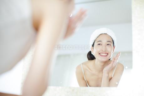 鏡の前でスキンケアをする笑顔の女性の写真素材 [FYI02966767]