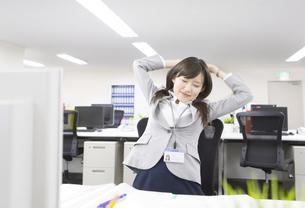 デスクで伸びをするビジネス女性の写真素材 [FYI02966768]