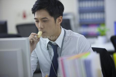 お菓子を手にパソコンを見るビジネス男性の写真素材 [FYI02966769]
