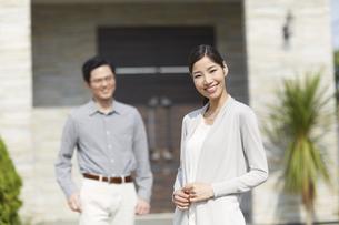 奥さんが手前で家の前に立つ夫婦の写真素材 [FYI02966774]