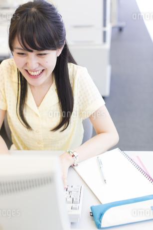 微笑みながらパソコンに向く女子学生の写真素材 [FYI02966775]