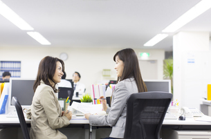 デスクで顔を見合わせるビジネス女性2人の写真素材 [FYI02966783]