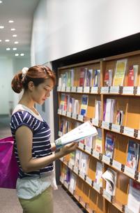 図書室で洋誌を読む女子学生の写真素材 [FYI02966785]