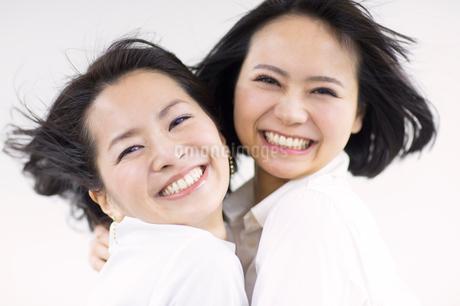 風を受けながら笑う女性2人の写真素材 [FYI02966786]