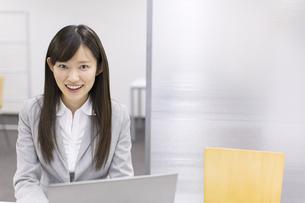 ノートパソコンの前で微笑むビジネス女性の写真素材 [FYI02966795]
