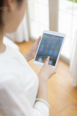 タブレットPCを操作する女性の写真素材 [FYI02966796]