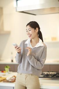 キッチンでスマートフォンを見ながら笑う女性の写真素材 [FYI02966797]