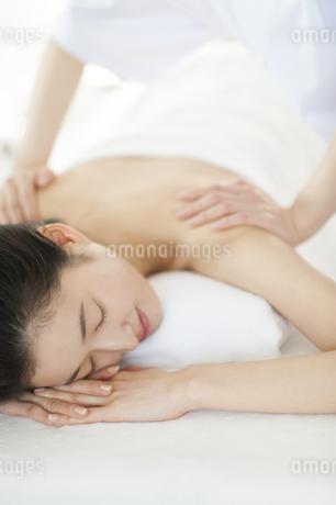 うつ伏せで肩をマッサージされている女性の写真素材 [FYI02966802]