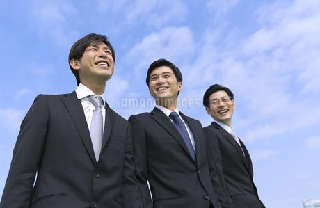青空を背景に笑う3人のビジネス男性の写真素材 [FYI02966803]