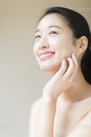 頬に片手を添えて上を見上げ微笑む女性の写真素材 [FYI02966805]