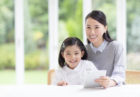 タブレットPCを手に微笑む母と娘の写真素材 [FYI02966809]