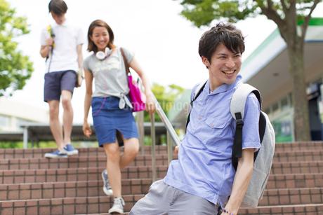 階段の手すりを滑る男子学生の写真素材 [FYI02966813]