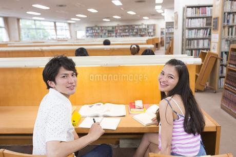 図書室で振り向いて笑う2人の学生の写真素材 [FYI02966815]