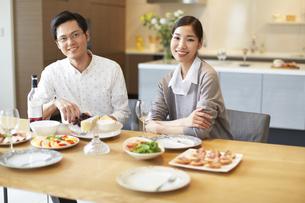 料理を前に微笑む男女のスナップの写真素材 [FYI02966816]