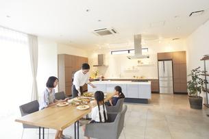 家族に食事を用意する父の写真素材 [FYI02966817]